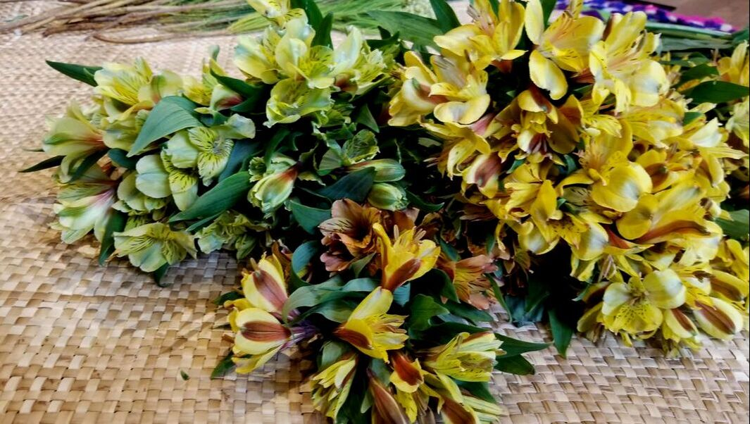 Yellow and green freesia over a lauhala mat in preparation for Kalei'okalani's Lei-Making Workshop at the Wing Luke Museum in Seattle's Chinatown-International District.